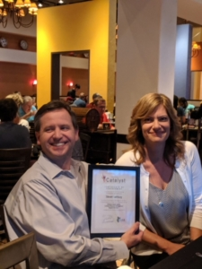 Image: Steve Isenburg holding an eCatalyst award he just received from his Program Manager, Leslie Eaton, at an employee recognition dinner.
